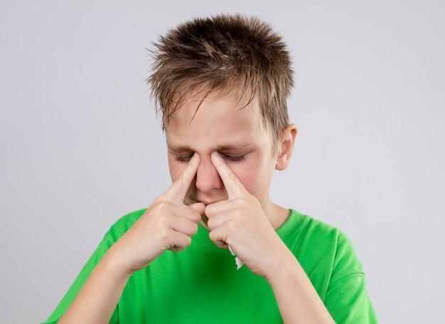Ziek jongetje in groen t-shirt zich onwel voelen wijzend met de vingers naar zijn neus met gesloten ogen staande over een witte muur