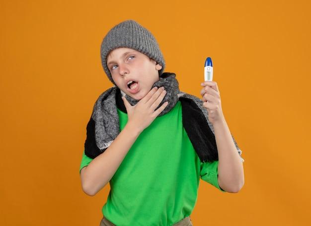Ziek jongetje met een groen t-shirt in een warme sjaal en een muts die thermometer toont die zich onwel voelt ziek en ongelukkig hand op zijn keel houdt die over oranje muur staat
