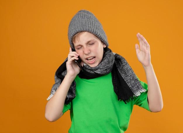 Ziek jongetje met een groen t-shirt in een warme sjaal en een muts, zich onwel voelen praten over de mobiele telefoon, ontevreden zijn met een geïrriteerde uitdrukking die over de oranje muur staat