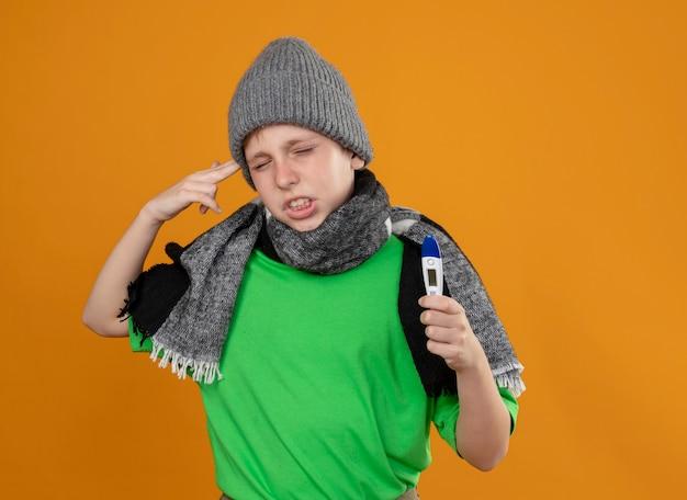 Ziek jongetje met groen t-shirt in warme sjaal en muts die thermometer toont die zich onwel voelt ziek en ongelukkig maakt pistoolgebaar in de buurt van tempel staande over oranje muur