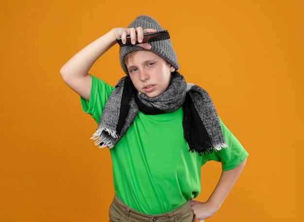 Ziek jongetje met groen t-shirt in warme sjaal en muts die zich onwel voelen en smartphone vasthouden die verward en ontevreden over de oranje muur staat