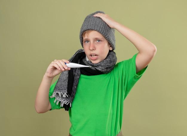 Ziek jongetje met groen t-shirt in warme sjaal en muts die zich onwel voelen met thermometer op zoek verward met temperatuur staande over lichte muur