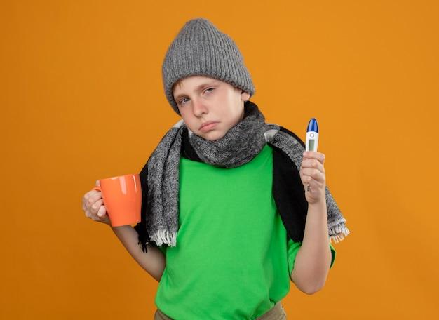 Ziek jongetje met groen t-shirt in warme sjaal en muts met kopje hete thee en thermometer zich onwel voelen ziek en ongelukkig staande over oranje muur