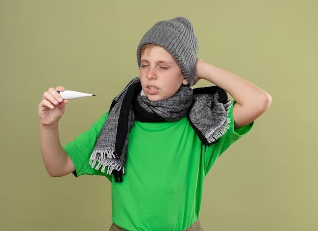 Ziek jongetje met groen t-shirt in warme sjaal en muts zich onwel voelen met thermometer kijken ernaar verward staande over lichte muur