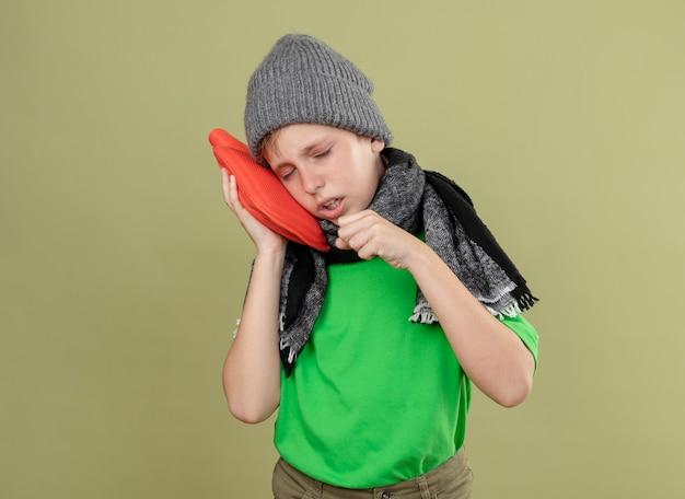 Ziek jongetje met groen t-shirt in warme sjaal en muts zich onwel voelen met waterfles om warm te blijven, leunend hoofd erop hoesten staande over lichte muur