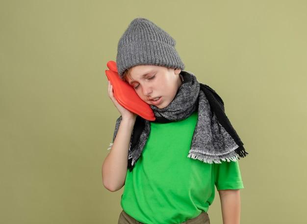 Ziek jongetje met groen t-shirt in warme sjaal en muts zich onwel voelen met waterfles om warm te houden, leunend hoofd erop, ziek en ongelukkig staande over lichte muur