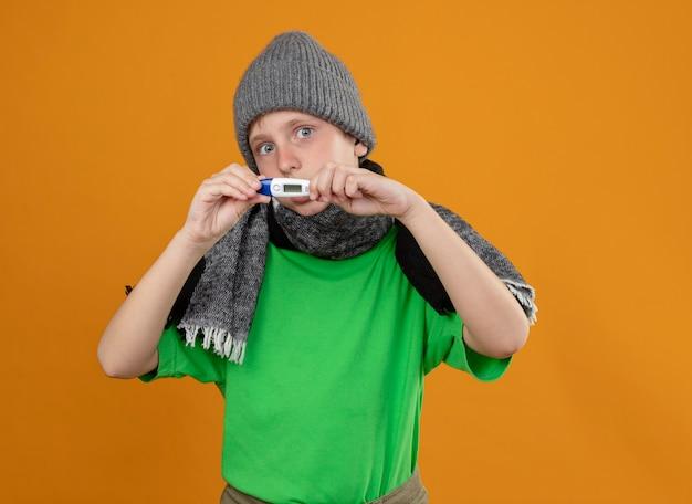 Ziek jongetje met groene t-shirt in warme sjaal en muts met thermometer die zich onwel voelt ziek en ongelukkig staande over oranje muur