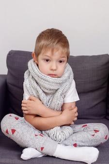 Ziek kind bevriest verpakt in een sjaal. de jongen wordt koud en zetelt thuis op de bank.