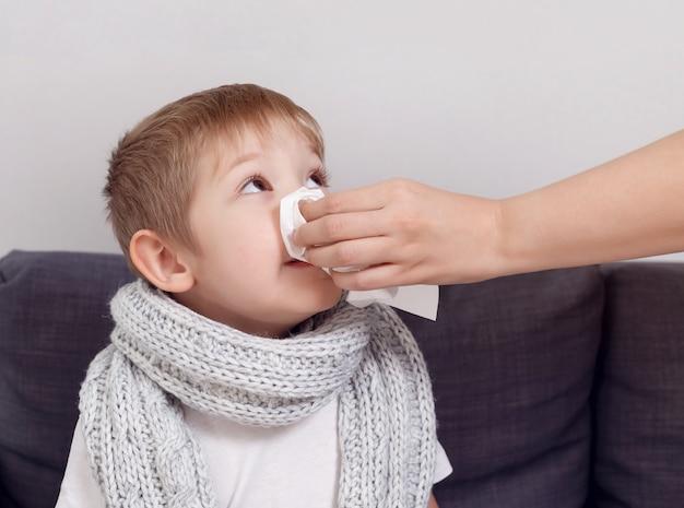 Ziek kind bevriest verpakt in een sjaal. de moeder van een zoontje gebruikt de zakdoek