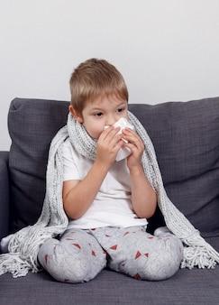 Ziek kind bevriest verpakt in een sjaal. kleine jongen gebruikt de zakdoek. de jongen wordt koud en snuit haar neus thuis op de bank.
