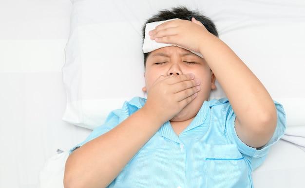 Ziek kind hoest en comprimeert op het voorhoofd.