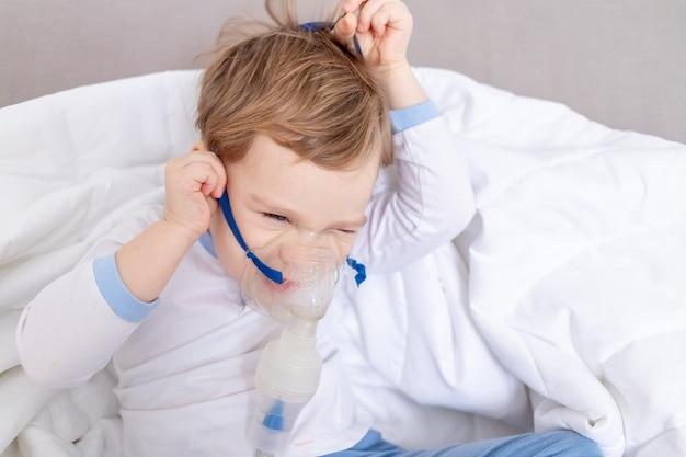 Ziek kind jongen neemt de inhalator af, wil niet thuis worden behandeld, het concept van gezondheid en inhalatiebehandeling