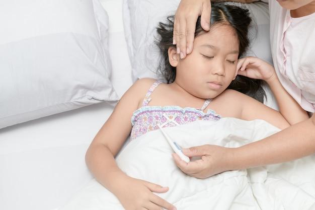 Ziek kind met hoge koorts in bed te leggen
