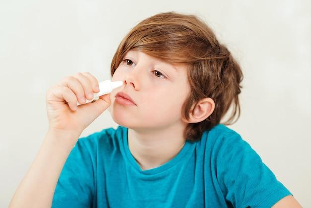 Ziek kind met loopneus dat neusspray gebruikt.