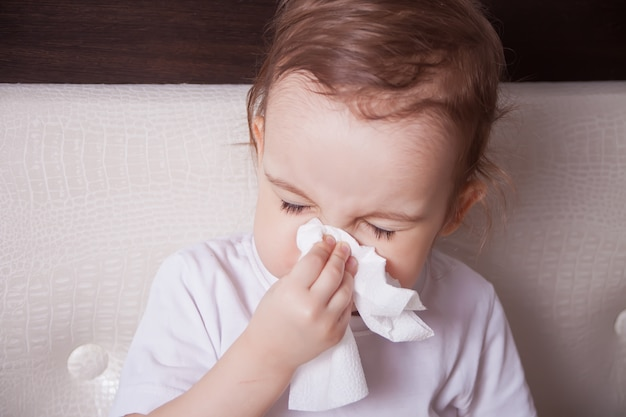 Ziek klein donkerbruin meisje dat haar neus blaast