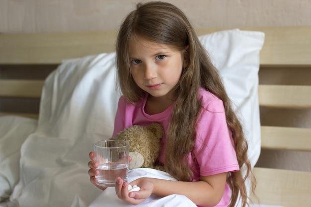 Ziek klein meisje met blond haar zit op het bed met glas waterpillen medicijnen in de buurt van teddy
