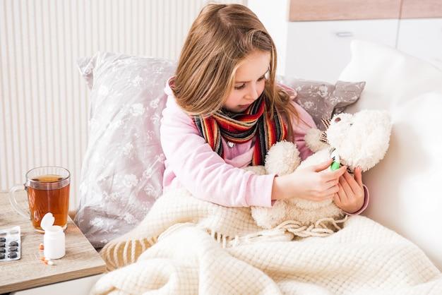 Ziek meisje dat de temperatuur van de teddybeer meet