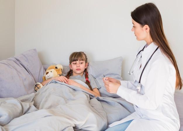 Ziek meisje dat door de arts wordt onderzocht