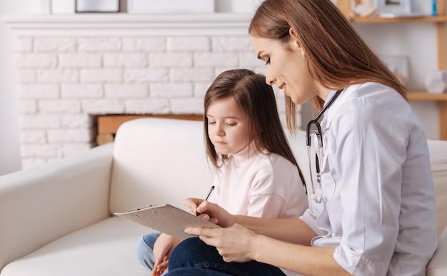 Ziek meisje dat een professionele dokter bezoekt terwijl ze een recept schrijft en haar advies geeft