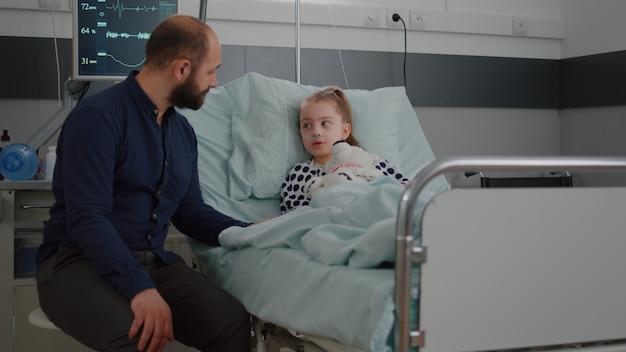 Ziek meisje dat in bed ligt en met bezorgde vader praat tijdens diagnoseoverleg