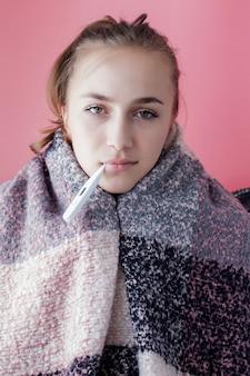 Ziek meisje dat met koorts kwikthermometer controleert op roze achtergrond.
