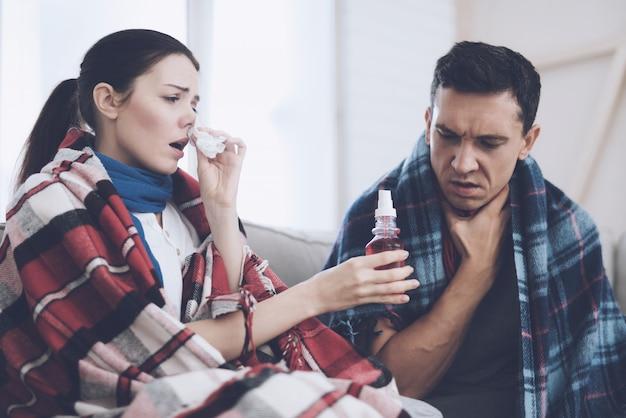 Ziek meisje dat neus druipt en druppels aan haar man overhandigt.