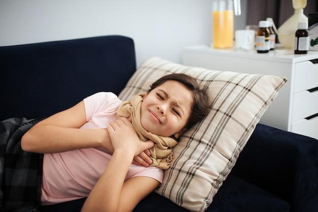 Ziek meisje dat op laag in alleen ruimte ligt. ze houdt handen op keel. meisje lijdt aan pijn. ze krimpt en houdt de ogen gesloten.