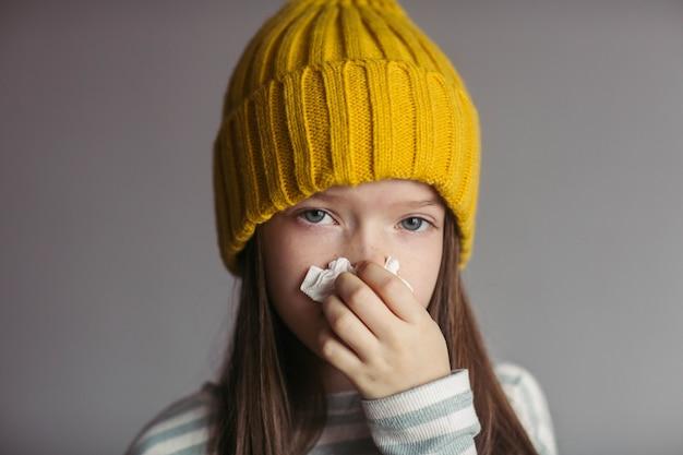 Ziek meisje in een hoed snuit haar neus