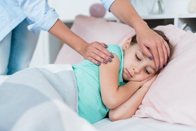 Ziek meisje liggend in bed onder een deken terwijl haar moeder het voorhoofd aanraakt om te zien of de temperatuur hoog is