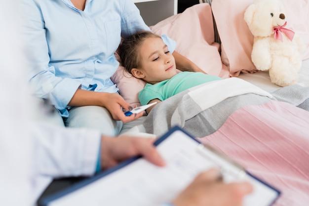 Ziek meisje liggend in bed onder een deken terwijl haar moeder thermometer en arts houdt die recepten maken