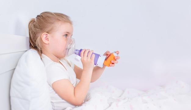 Ziek meisje met astmageneeskunde die in bed liggen. onwel kind met kamerinhalator voor hoestbehandeling. griepseizoen. slaap- of ziekenhuiskamer voor jonge patiënten. gezondheidszorg en medicatie.