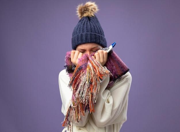 Ziek meisje met gesloten ogen dragen witte mantel en muts met sjaal met thermometer en bedekt gezicht met sjaal geïsoleerd op paars