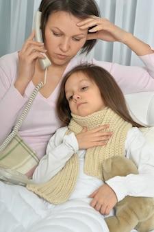 Ziek meisje met moeder in bed thuis
