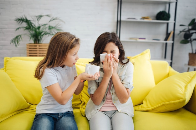 Ziek meisje op rechte zit op bank en niesgeluid. ze lijdt. het meisje links geeft haar witte beker. ze probeert haar te helpen. ze zitten op een gele bank in de kamer.