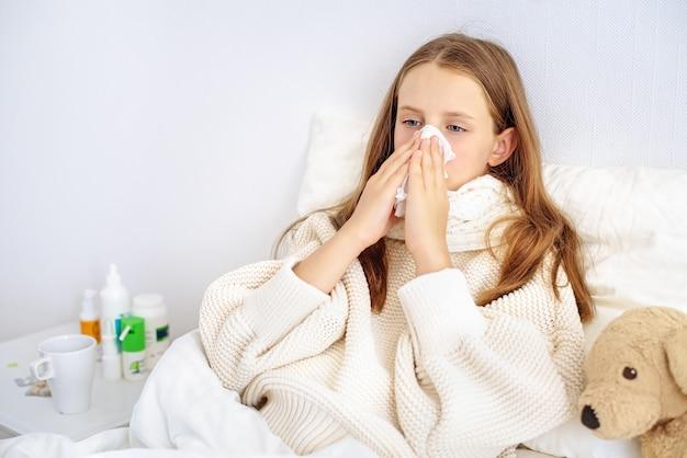 Ziek meisje snuit haar neus in een zakdoek zittend op het bed.
