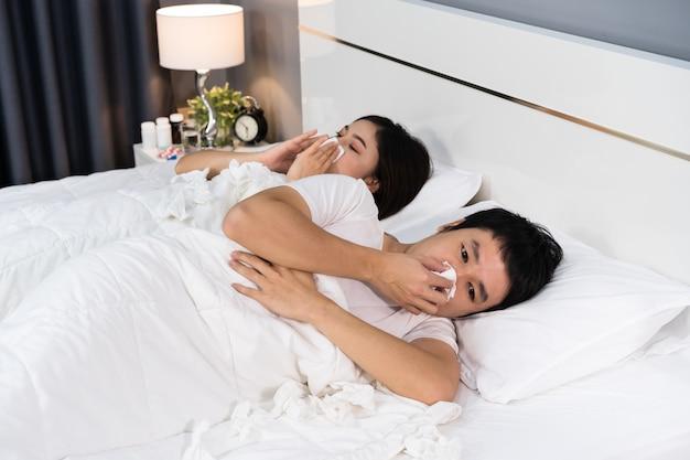 Ziek paar niezen en lijden aan virusziekte en koorts op bed