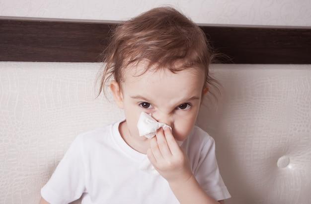 Ziek schattig klein meisje blaast haar neus