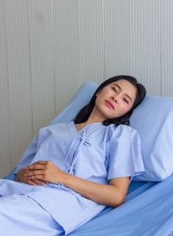 Ziek uitgeput ongelukkig aziatisch wijfje ligt ongelukkig op bed in het ziekenhuis.