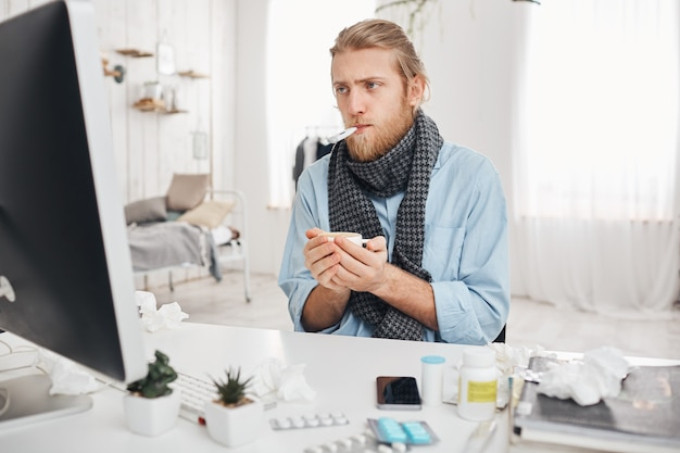 Ziek zieke bebaarde man zit achter computerscherm met thermometer in mond, meet temperatuur, houdt een kop warme drank in zijn handen. trieste jonge blonde man heeft een zware verkoudheid of griep