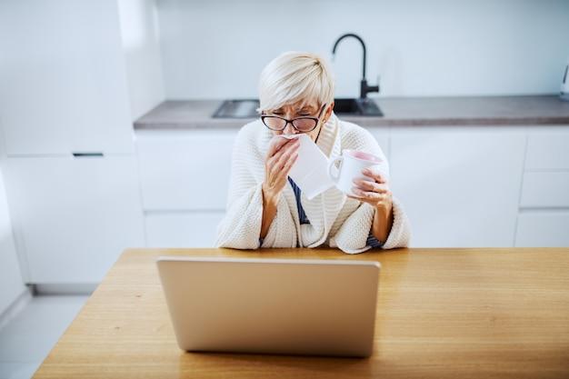 Zieke aantrekkelijke blonde senior vrouw bedekt met deken met mok met thee, neus afvegen en kijken naar laptop zittend aan eettafel
