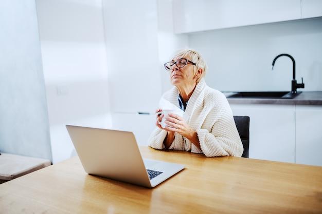 Zieke aantrekkelijke blonde senior vrouw bedekt met deken zittend aan eettafel en mok met thee en zakdoek te houden