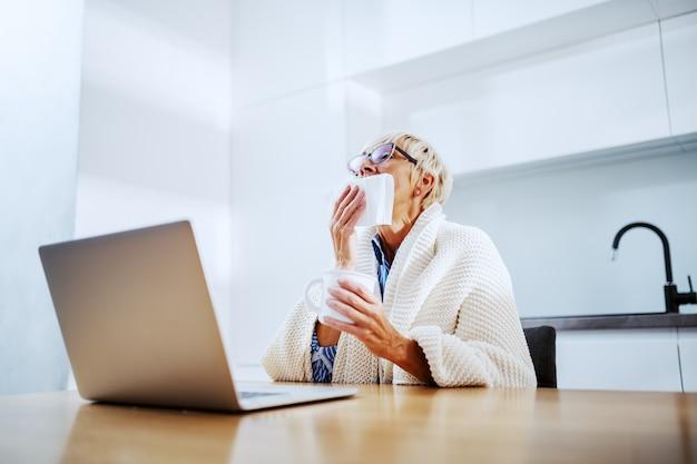 Zieke aantrekkelijke blonde senior vrouw bedekt met een deken aan eettafel zitten en niezen