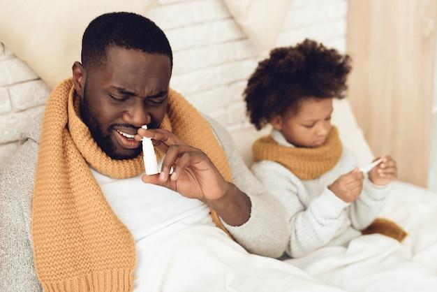 Zieke afrikaanse amerikaanse vader en dochterzitting op bed.