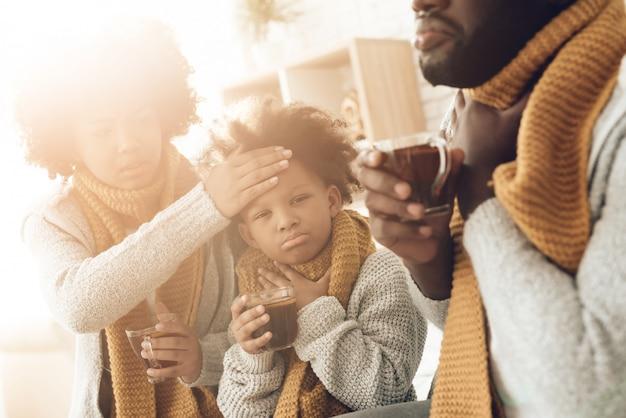 Zieke afrikaanse familie met keelpijn die op bed thuis zitten