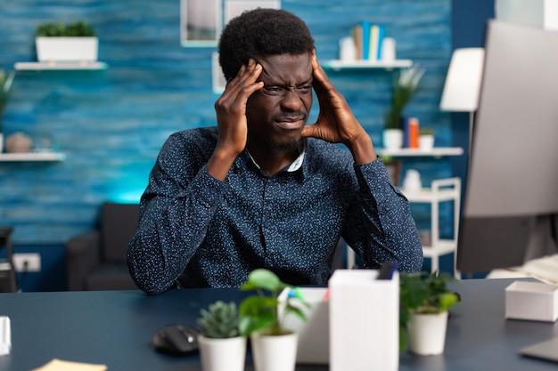 Zieke afro-amerikaanse man die stress heeft over deadline