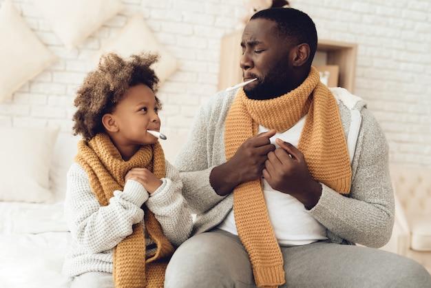 Zieke amerikaanse vader en dochter met temperatuur.