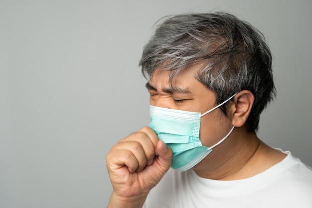 Zieke aziatische man die een medisch gezichtsmasker draagt en hoest en zijn mond bedekt met mijn hand