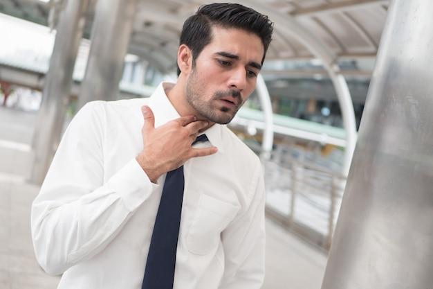 Zieke aziatische man hoesten; portret van zieke, zieke aziatische indiase man met keelpijn, ontsteking
