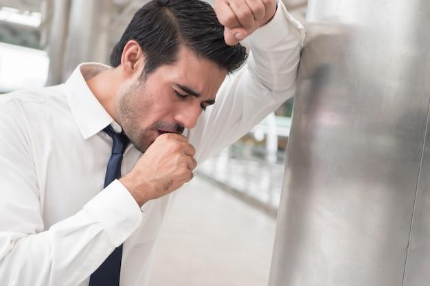 Zieke aziatische man hoesten; portret van zieke, zieke aziatische indiase man met keelpijn?