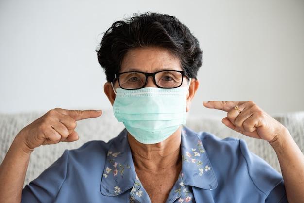 Zieke aziatische oude vrouw die beschermend gezichtsmasker draagt